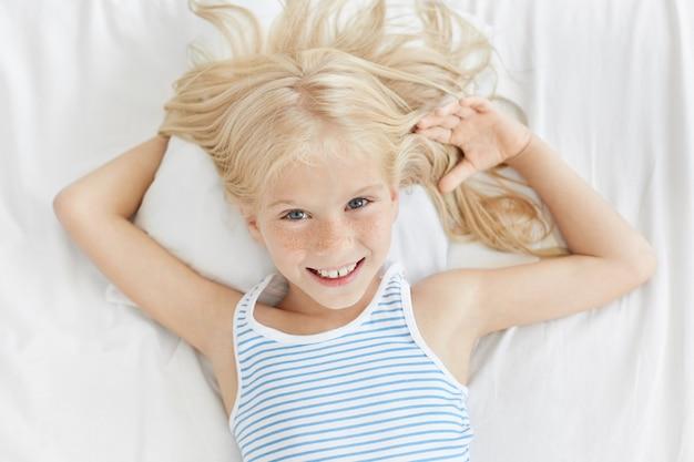 Horizontales porträt des niedlichen mädchens mit blau leuchtenden augen, sommersprossigem gesicht und sanftem lächeln, entspannend im bett, liegend auf bequemem weißem kissen