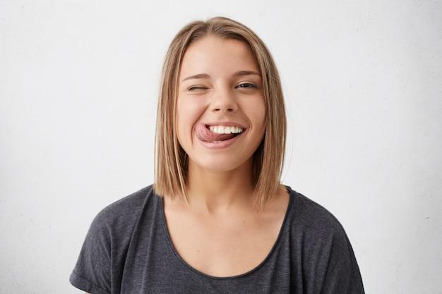Horizontales porträt des optimistischen lustigen mädchens mit bob-frisur, die ihre zunge und blinkende augen zeigt