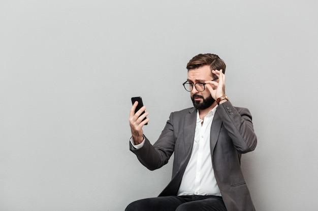 Horizontales porträt des stilvollen geschäftsmannes rührende brillen des smartphone beim sitzen betrachtend auf stuhl im büro, lokalisiert über grau