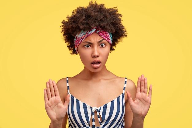 Horizontales porträt einer attraktiven jungen frau mit afro-frisur, dunkler gesunder haut, empörtem missfallenem gesichtsausdruck, zeigt ablehnungsgeste, isoliert über gelber wand. hör auf!