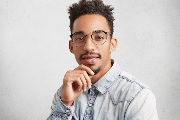 Horizontales porträt eines dunkelhäutigen mannes mit trendiger frisur, trägt jeanshemd und runde brille