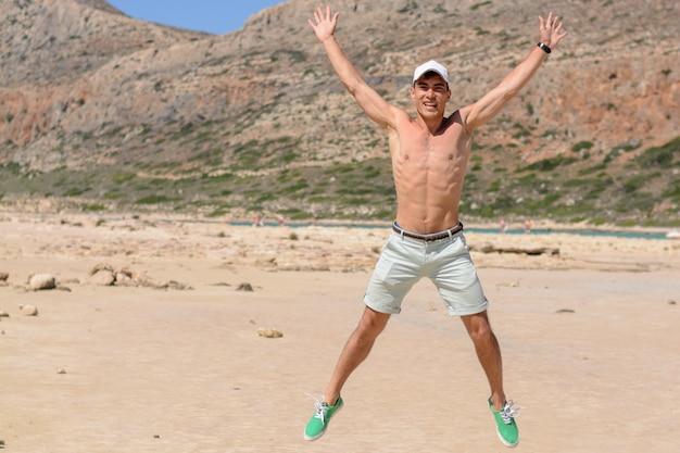 Horizontales porträt eines jungen mannes im urlaub, glückliches springen oben auf den strand. copyspace