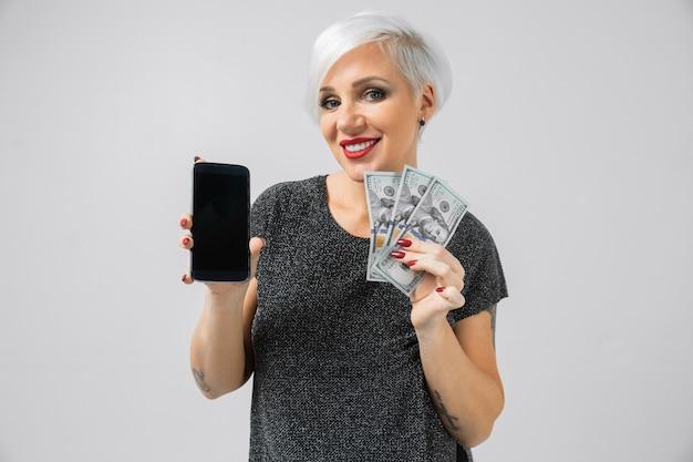 Horizontales porträt von erwachsenen blondinen mit smartphone und stapel geld