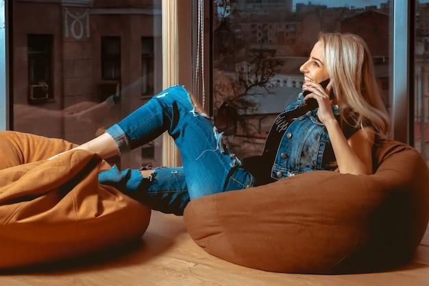 Horizontales profilporträt der jungen blonden frau der schönheit, die telefon spricht und lächelt. konzept der entspannung, erfrischung und freizeit