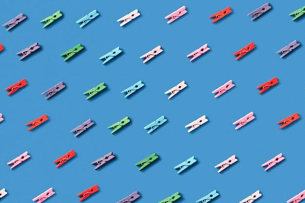 Horizontales wäschemuster von bunten wäscheklammern auf einer blauen wand. draufsicht.
