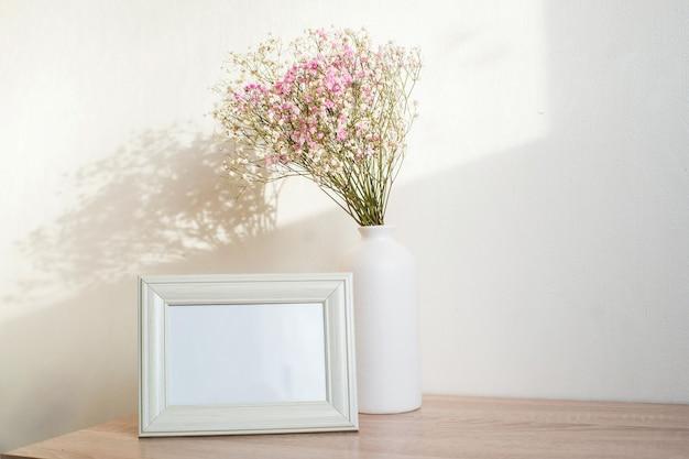 Horizontales weißes rahmenmodell auf weinlese-holzbank, tisch. moderne weiße keramikvase gypsophila. weißer wandhintergrund.