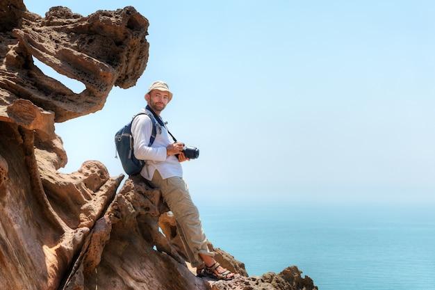 Hormuz island, hormozgan, iran, reisender mit kamera sitzt am rand der klippe.