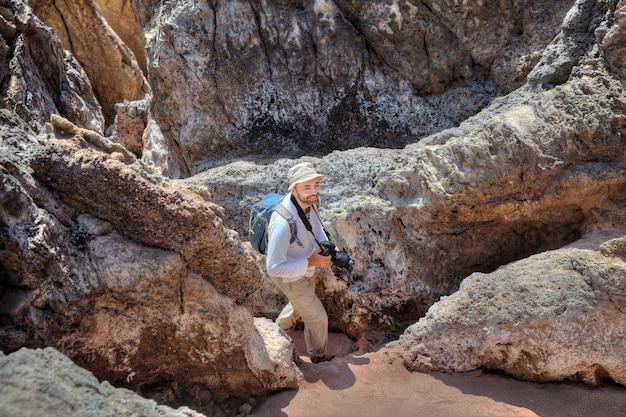 Hormuz island iran, ein rucksacktourist geht auf dem kopf den bergweg entlang, hält die kamera in den händen und hat den rucksack hinter sich. Premium Fotos