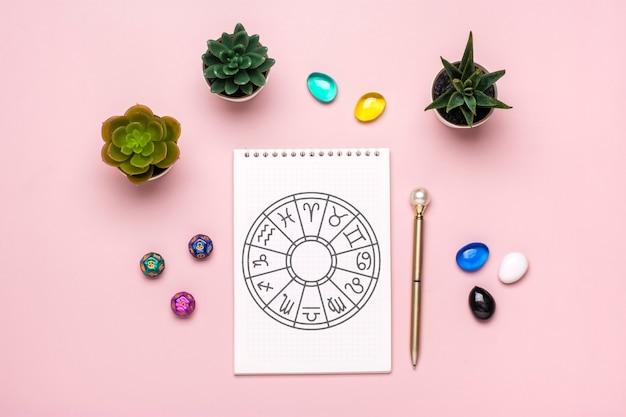 Horoskopkreis mit zwölf tierkreiszeichen auf papier weissagungswürfel bunter stein auf rosa hinterg...