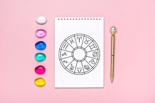 Horoskopkreis mit zwölf tierkreiszeichen auf papier, weissagungswürfel, bunter stein auf rosa hintergrund wahrsagerei und astrologische vorhersagen draufsicht flache lage.