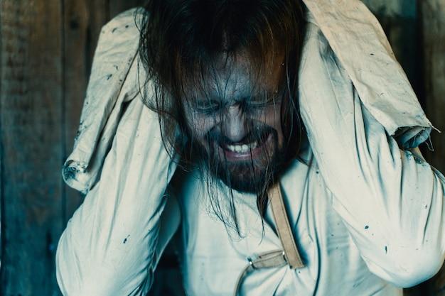Horror für halloween-feiertag verrückter mann in einem schmutzigen messhemd in einem alten zerstörten haus ist verschlossen und erschreckt alle, die ein opfer erwarten