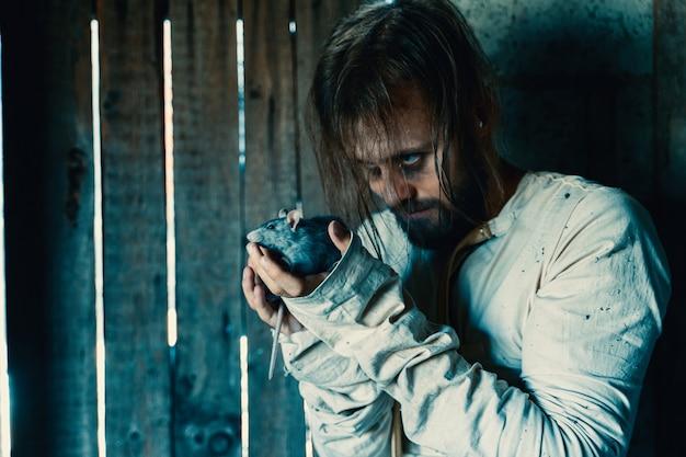 Horror für halloween-urlaub verrückter mann in einem schmutzigen messhemd in einem alten zerstörten haus ist verschlossen und erschreckt alle, die ein opfer mit ratte erwarten