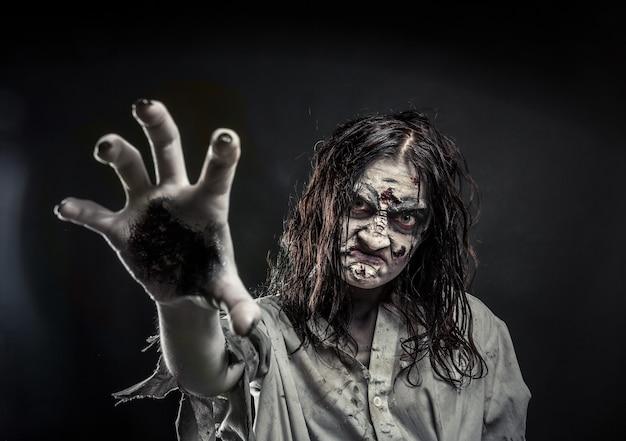 Horror-zombie-frau mit blutigem gesicht, die dir die hand reicht