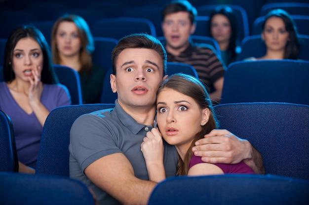Horrorfilm gucken. schockiertes junges paar, das sich beim anschauen eines films im kino