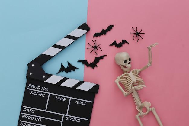 Horrorfilm, halloween-thema. filmklappe, skelett, spinnen und fliegende dekorative fledermäuse auf rosa blauem pastell