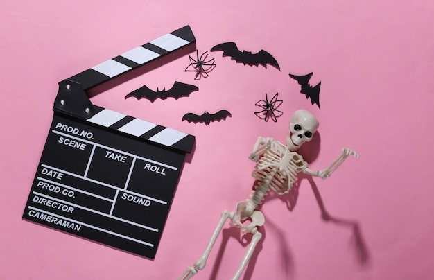 Horrorfilm, halloween-thema. filmklappe, skelett, spinnen und fliegende dekorative fledermäuse auf rosa hell