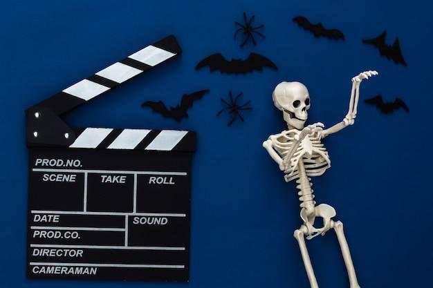 Horrorfilm, halloween-thema. filmklappe, skelett, spinnen und fliegende zierfledermäuse auf klassischem blaudunkel