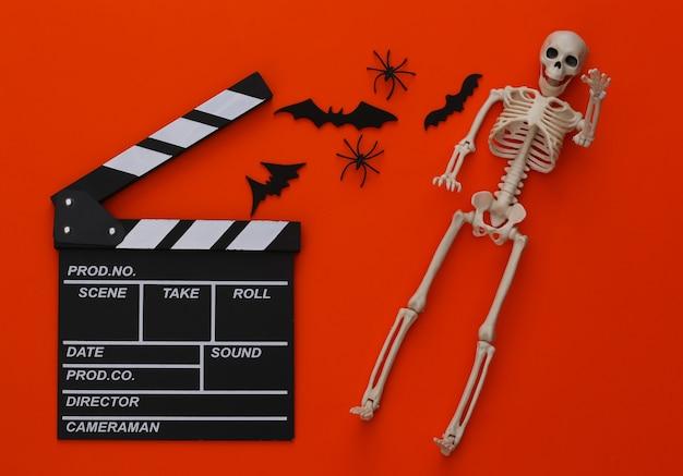 Horrorfilm, halloween-thema. filmklappe, skelett, spinnen und fliegende zierfledermäuse auf orange