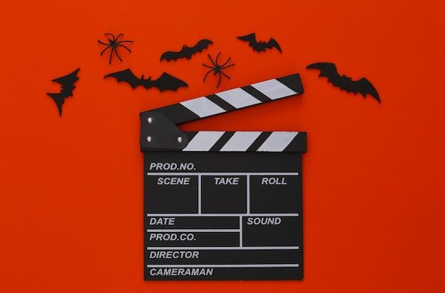 Horrorfilm, halloween-thema. filmklappe, spinnen und fliegende zierfledermäuse auf orange