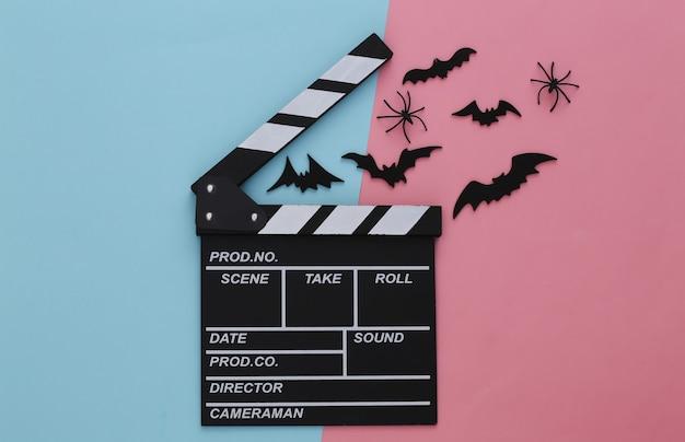Horrorfilm, halloween-thema. filmklappe und fliegende dekorative fledermäuse, spinnen auf rosa blauem pastell
