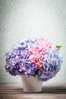 Hortensienblüten im weißen eimer auf dem holztisch