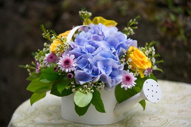 Hortensienblumenanordnung in der gießkanne. hochzeitsdekoration. sommerdekor im freien.