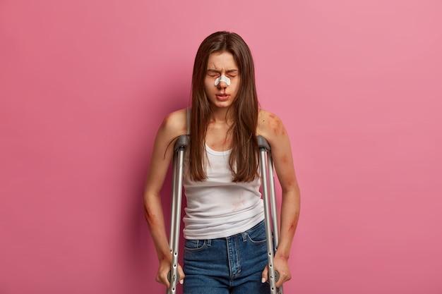 Hospitilisierte frau hat rehabilitationsphase nach schwerem unfall, verschiedene frakturen, posiert auf krücken, leidet an schwerer wirbelsäulenerkrankung, verletzt nach autounfall, hat sich die blutende nase gebrochen