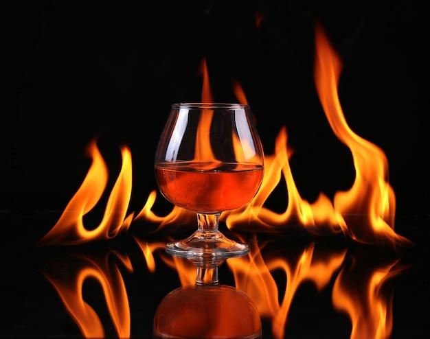 Hot chili pfeffer in einem cognac-ballon mit einem feuer auf einem schwarzen hintergrund