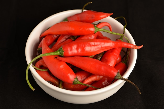 Hot chili pfeffer in weißen keramiktopf mit schwarz