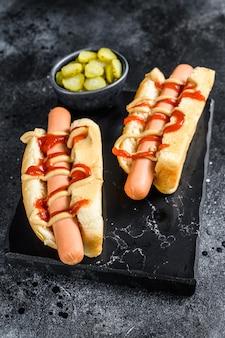 Hot dog mit gelbem senf und rotem ketchup. schwarzer hintergrund. draufsicht.