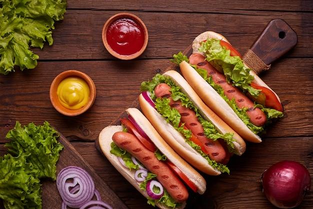 Hot dog mit gurken, tomate und salat auf hölzernem hintergrund. draufsicht