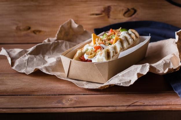 Hot dog mit käse, wurst, röstzwiebeln, gemüse und soße