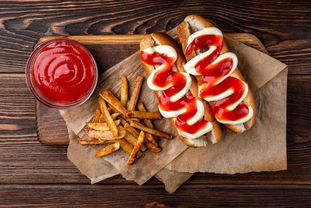 Hot dog mit mayonnaise und ketchup und pommes frites auf dunklem holzhintergrund.