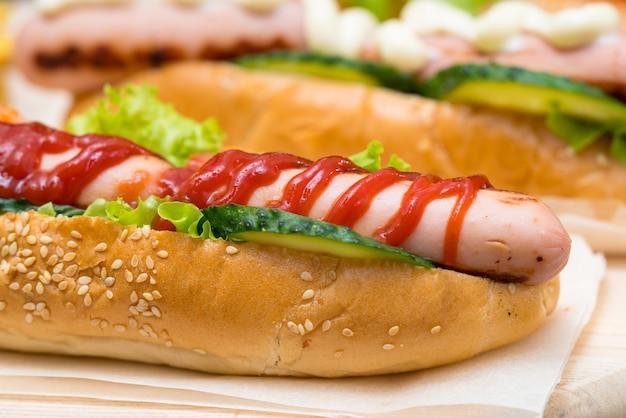 Hot dog mit tomatenketchup beträufelt und mit frischer gurke und salat auf einer frischen sesamrolle in nahaufnahme serviert