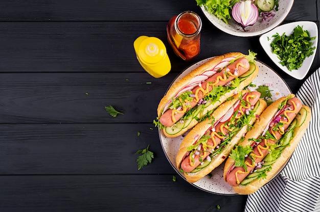 Hot dog mit wurst, gurke, radieschen und salat