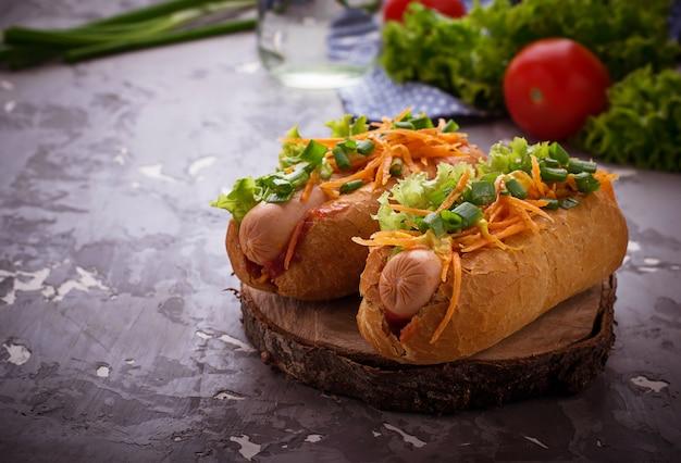 Hot dog mit wurst, karotten, zwiebeln, salat