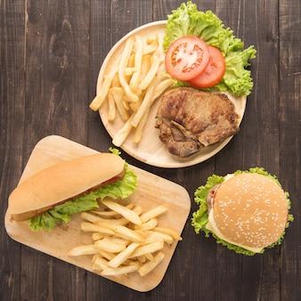 Hot dogs, hamburger und gegrilltes schweinekotelettsteak auf dem holz