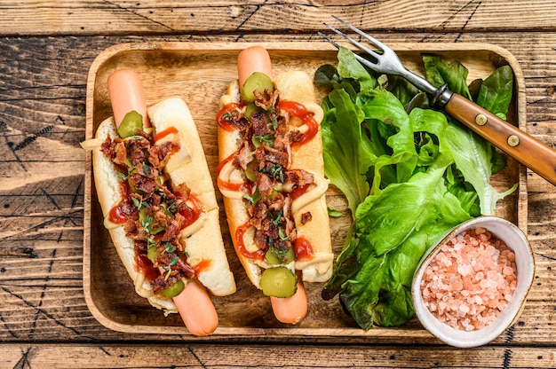 Hot dogs mit gebratenem speck, zwiebeln und eingelegten gurken. hölzerner hintergrund. draufsicht.
