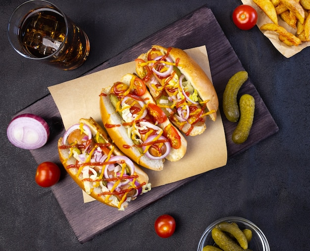 Hot dogs mit gemüse, senf und ketchup auf einem schneidebrett auf dunklem hintergrund, ansicht von oben