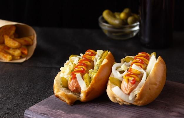 Hot dogs mit gemüse, senf und ketchup auf einem schneidebrett auf dunklem hintergrund