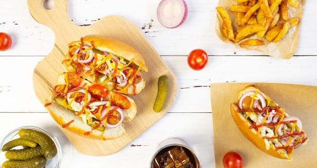 Hot dogs mit gemüse, senf und ketchup auf einem schneidebrett auf einem weißen holztisch, ansicht von oben