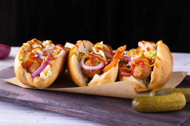 Hot dogs mit gemüse, senf und ketchup auf einem schneidebrett, seitenansicht fast food, street food