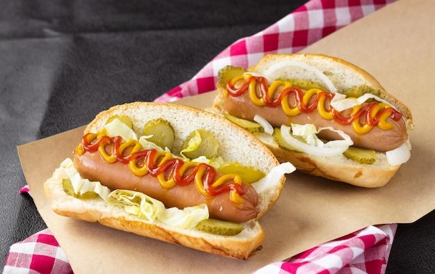 Hot dogs mit gemüse, senf und ketchup auf lebensmittelpapier und einem karierten handtuch, seitenansicht