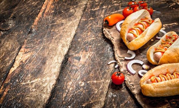 Hot dogs mit senf, zwiebeln und tomaten. auf einem holztisch.