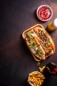Hot dogs mit verschiedenen würzigen belägen, dunkler hintergrund mit kopienraum, vertikal