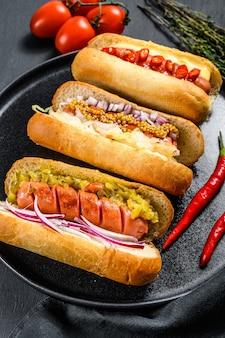 Hot dogs voll beladen mit verschiedenen belägen auf einem tablett