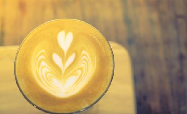 Hot latte art kaffee auf dem tisch (gefiltertes bild verarbeitet jahrgang