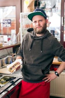 Hotdog - freundlicher verkäufer und frische zutaten in einer fast-food-snackbar