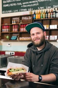 Hotdog - freundlicher verkäufer und kunde in einer fast-food-snackbar