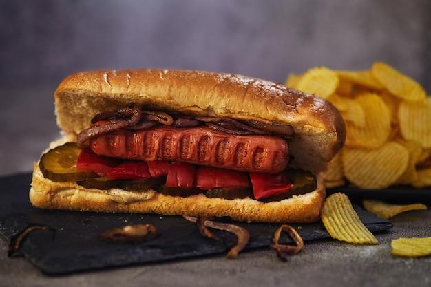 Hotdog - heiße wurst verschachtelt in einem brötchen mit gurken, rotem pfeffer und zwiebeln.